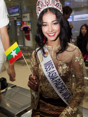 In this June 5, 2014 file photo, Myanmar model May Myat Noe, winner of Miss Asia Pacific World 2014 pageant, waves a miniature flag of the country upon her arrival at Yangon International Airport in Yangon, Myanmar. The first Myanmar national to win an international pageant has been stripped of her title for being rude and dishonest, and has allegedly run off with the expensive crown and breast implants.