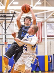 Wyoming senior Jake Edmonds shoots the ball over Jacob McFarland of Madeira.
