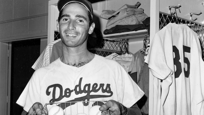 Sandy Koufax holds a basket of 20 baseballs representing his 20th win of 1965. He won 26 that year.