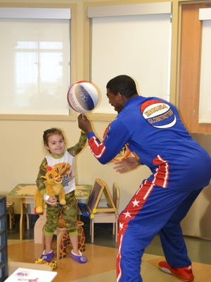 Buckets Blake, a member of the Harlem Globetrotters, helps a patient in the Lafayette General Medical Center pediatrics ward how to spin a basketball on her finger.