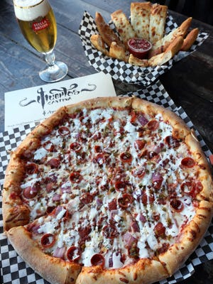 The Rodrigo Rodriguez pizza comes with pepperoni, bacon, red onions, minced jalapeno and goat cheese. And don't forget the cheese bread.
