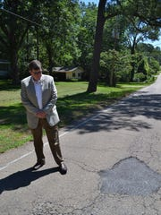 In this June, 2016 photo, lawyer William Smith is seen with a pothole he filled. At the time of photo, Smith reported he had been filling potholes near his home on Meadowbrook Road in Jackson, Miss. for years.