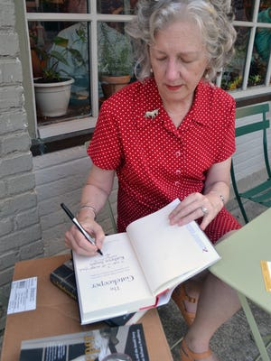Anderson resident Kathryn Smith signs her latest book for her former coworker Linda Kinney of Anderson Thursday night at the book signing event.