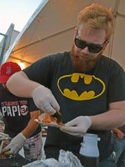 Brad Cox with SummaJoe's serves up steak chimichurri at the FreshTaste festival Tuesday night.