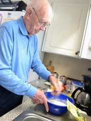 George Leitner, 99, makes muffins Wednesday for Thanksgiving breakfast with his family.