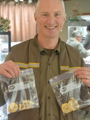 Dwight Patton, a UPS driver, holds cookies given to him by a customer during the holiday season.