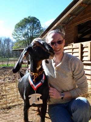 Farm manager Jessica Bell poses with one of her dairy goats Pepper, at Split Creek Farm, this month.