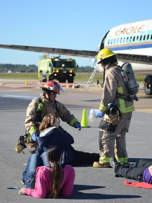 Members of the AEX fire department help victims of the mock crash of an airplane during a multi-agency training exercise at AEX on Wednesday.