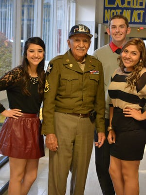 Army veteran Frank Ramirez is welcomed by students Vanessa Lopez (left), Brandon Gieselman (back) and Magaly Martinez (right) during Living History Day on Nov. 6, 2014, at Gervais High School. Ramirez earned a Silver Star during the Korean War.