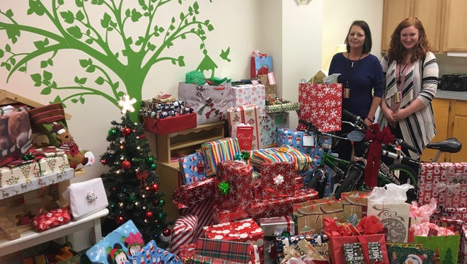 Heather Hudnall and Lauren Wimer, of Shenandoah Valley Social Services, pose with a crop of donated Christmas gifts set for delivery to area foster homes on Monday, Dec. 18, 2017, at the agency office in Verona, Virginia.