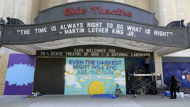 Artists commissioned by CAPA work to create murals on the plywood covering the front of the Ohio Theatre in downtown Columbus on June 2. Murals like this will be preserved online by a new website.