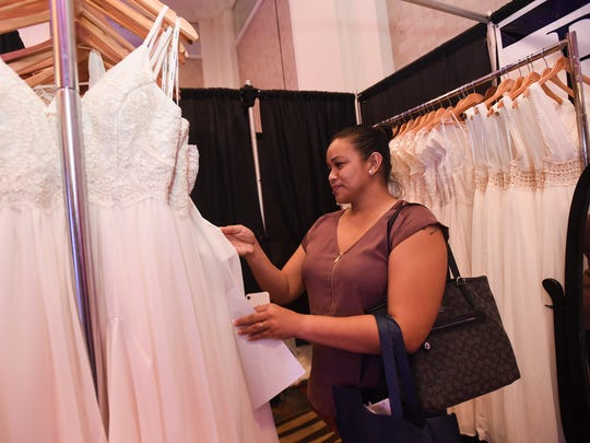 Bride-to-be Julie Duay checks out the dress selection selection at the Budget Bridal Boutique booth during the 18th Annual Weddings in Paradise show at the Sheraton Laguna Guam Resort on March 24, 2018.