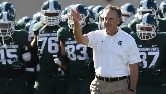 Michigan State head coach Mark Dantonio leads his players over to the student section before action against Michigan on Saturday, Oct. 25 ,2014 at Spartan Stadium.