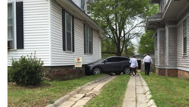 A woman was being treated by EMS this afternoon after her car hit a house on Campbell Street at McCowat.