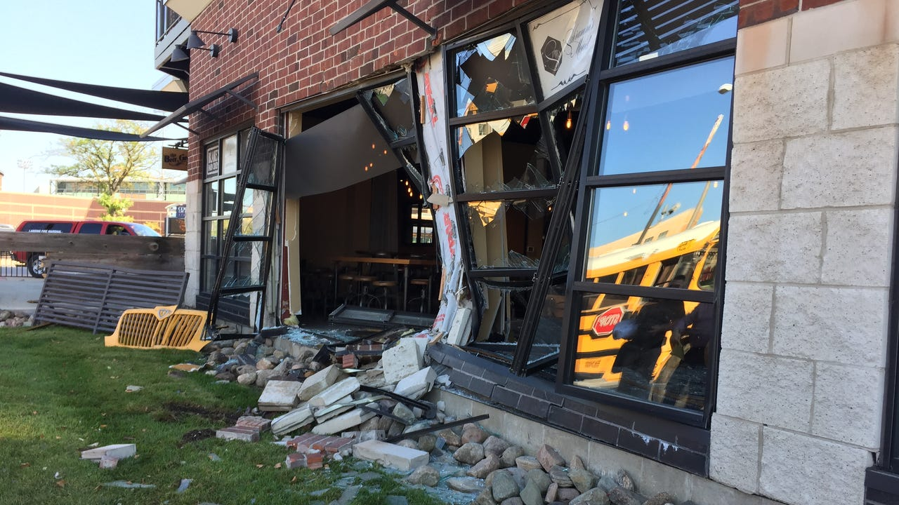 Crews remove a school bus that crashed into a building at Cedar and Michigan in Lansing on Tuesday morning.