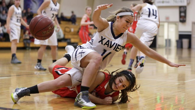 Kayla Gresl of Xavier (top) and Marina Solberg of New London collide going after a loose ball in a Bay Conference basketball game Saturday in Appleton.