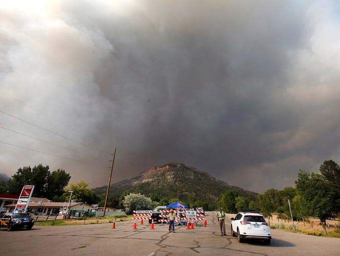 Smoke rises from the 416 Fire behind the U.S. Highway