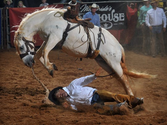 Lane Sharp of the Waggoner Ranch hits the ground hard and a little early before scoring in the ranch bronc riding competition at the Texas Ranch Roundup in 2016.