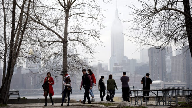 People walk through a park along the East River with the Empire State Building in the background during a warm Christmas Day in Brooklyn, New York, on Dec. 25, 2015.