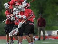 Penfield players mob their goalie Liam Guiton (24), left, after the final whistle as following a Class A sectional semifinal played at Eastridge High School on Friday, May 24, 2013.  No. 4 seed Penfield beat No. 4 seed Fairport, 10-8, to advance to the Class A championship game.