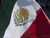 A demonstrator holds a Mexican flag during a march n Mexico City, Monday, Dec. 3, 2012.