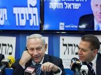 A worker hangs a huge poster with an image of Israel's Prime Minister Benjamin Netanyahu in Tel Aviv.