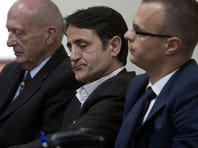 Kosovo Albanian doctor Lutfi Dervishi, center, flanked by defense councils, sits in a court room,  in Pristina,  Kosovo, Monday, April 29, 2013.
