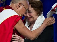 The Dalai Lama puts on a Maryland visor before delivering the Sadat Lecture for Peace at the University of Maryland in College Park on May 7, 2013.