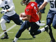 Seattle Seahawks quarterback Russell Wilson rushes during minicamp practice at the Virginia Mason Athletic Center in Renton, Wash. on June 12, 2013.