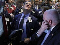 Trader Sean Spain, center, checks prices on the floor of the New York Stock Exchange.