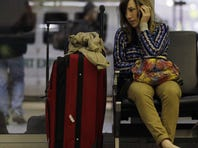 A traveler talks on her phone while waiting at O'Hare International Airport in Chicago.