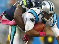 Chris Clemons (91) and the Seahawks defense held Cam Newton (1) and the Panthers to 190 yards of total offense.