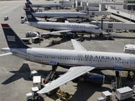 In this Sept. 27, 2012 photo, US Airways jets are parked at Charlotte/Douglas International Airport.