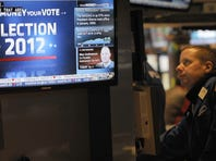A trader watches the news on the floor of the New York Stock Exchange Nov. 7, 2012, a day after President Obama was re-elected.