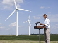As wind turbines turn in the distance, President Obama speaks at the Heil family farm on Aug. 14, 2012, in Haverhill, Iowa. Obama supports the renewal of a tax credit for large-scale wind producers, slated to expire at the end of 20112.