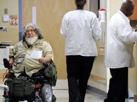 Vietnam veteran Jesus Quintana Jr., left, 63, of Indianapolis, makes his rounds at the Roudebush VA Medical Center in Indianapolis as a volunteer.