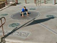 A boy touches four border states, New Mexico, Arizona, Utah and Colorado at Four Corners National Monument.