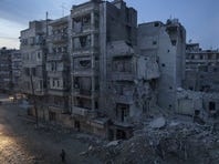 Night falls on a Syrian rebel-controlled area as destroyed buildings, including Dar Al-Shifa hospital, are seen on Sa'ar street.