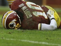 Washington Redskins quarterback Robert Griffin III touches his back after a sack by Baltimore Ravens defensive end Arthur Jones during the second half Sunday, Dec. 9, 2012.