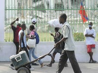 People walk in front of the National Presidential Palace in Port au Prince, Haiti, in 2009.