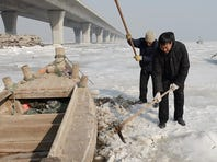 Fishermen try to dig out a fishing boat trapped in ice in the Jiaozhou harbor in Qingdao, in east China's Shandong province, on Jan. 5.