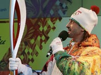 Russian ice dancer Ilia Averbukh presents the Olympic torch and uniform for the relay of the Olympic and Paralympic flame for 2014 Sochi Winter Olympics, in Moscow, Russia, on Monday.