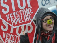 Walken Schweigert, 24, of Minneapolis, right, and Anna Cole, 26, of Rochester, N.Y.,  hold signs protesting the Keystone Pipeline near the Washington Monument during a climate change rally in Washington on Sunday.