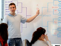 Matt Trogdon, business community connector at Motley Fool, teaches a class on the NCAA Tournament to his co-workers.  Motley Fool embraces March Madness and offered the class so workers would know how to pick teams for their tournament brackets.