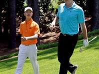 Amateur Guan Tianlang, of China, walks with Nick Faldo, right, during the Par-3 competition before the Masters golf tournament Wednesday.