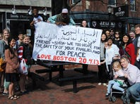 Gathered in Somerville, Mass., Bostonians display a message of peace and safety for Syrians who sent their condolences the day before.