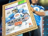 NFL Hall of Fame running back Barry Sanders holds a mock-up of the Madden NFL 25 video game cover during the EA Sports Madden NFL 25 Cover Reveal in New York.