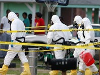 Federal authorities wearing hazmat suits walk to the home of Everett Dutschke April 23 in Tupelo, Miss., in connection with the recent ricin attacks.