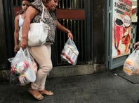 A customer leaves a private supermarket with her purchases, including toilet paper, in Caracas, Venezuela, on May 15.