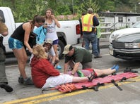 Emergency personnel respond to one of the people hit by a car, at right, during the beginning of the Hikers Parade at the Trail Days festival in Damascus, Va., Saturday.